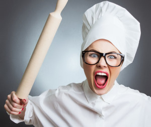 Angry woman cook trying to hit with a rolling pin over a gray background. Funny photo
